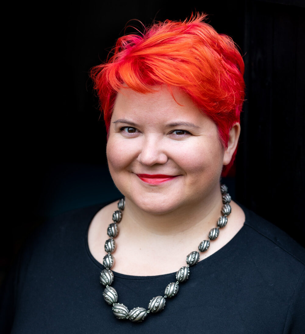 Portrait of Lisa Riemers, a woman with short, bright orange hair, wearing a bold silver necklace, smiling at the camera